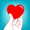 Human hand holding red heart up.