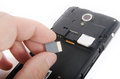 Human hand inserting micro sd card into cell phone smartphone Stock Image