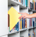 Human hand taking a book  in a library Stock Photos