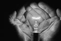 Human hands holding a light bulb to conserve energy darkness art Royalty Free Stock Photos