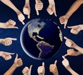 Human hands showing thumbs up around earth planet Royalty Free Stock Photo
