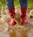 Human legs splashing in a muddy puddle Stock Photo