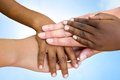 Human races joining hands close up of multiethnic children s making pile against blue sky Royalty Free Stock Photos