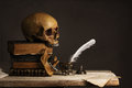 Human Skull on old Books with empty Page, Feather and Inkpot Royalty Free Stock Photo
