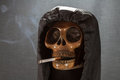 Human skull smoking a cigarette on a black background, Cigarette very dangerous for people. Please don't smoke.Halloween day Royalty Free Stock Photo