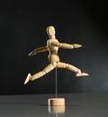 Human wood manikin jumping against dark background Stock Photography