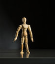 Human wood manikin is standing against dark background Stock Images