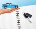 Humans hand holding car with open notebook Stock Photo