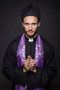 Humble priest with christian cross studio portrait on black background Stock Photos