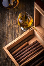 Humidor with quality cigar and cognac on an old wooden table Stock Photography