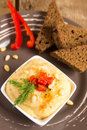 Hummus in a bowl with vegetables red pepper pine nuts and bread close up vertical Stock Images