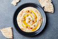 Hummus, chickpea dip, with spices and pita, flat bread in a black plate. Top view Royalty Free Stock Photo