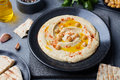 Hummus, chickpea dip, with spices and pita, flatbreadin a black plate on grey stone background. Royalty Free Stock Photo
