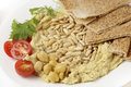 Hummus with roasted pine nuts and lightly dip garnished cherry tomatoes and young salad leaves viewed close up Royalty Free Stock Photos