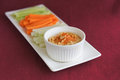 Hummus and vegetables with carrot cucumber celery on white plate on red background Stock Images
