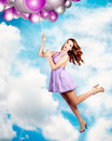 Humorous beautiful pin up girl flying cloud filled sky holding onto rope helium party balloons birthday celebration concept Stock Photos