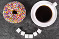 Humorous donut and coffee cup on slate board top view Royalty Free Stock Images
