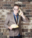 Humorous male nerd chatting business on phone engaging in chatter with discussions of retro revival brick wall background Stock Image