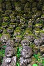 Humorous rakan stone buddha statues with funny faces partially covered by greenery Stock Photo
