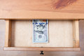 Hundred dollar banknotes pack in open drawer above view of of nightstand Royalty Free Stock Photography