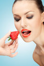 Hunger for berries a creative portrait of a beautiful girl being fed with a red ripe strawberry Stock Photography