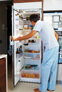 Hunger: Mature man opening the refrigerator door Stock Image