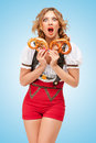 Hunger for pretzels young sexy swiss woman wearing red jumper shorts with suspenders in a form of a traditional dirndl holding Stock Photos