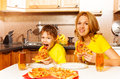 Hungry boy and his mother eating pizza in kitchen funny together at the table the Royalty Free Stock Photos