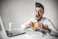 Hungry businessman working during lunch break looking at his hamburger while Royalty Free Stock Photography