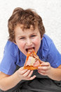 Hungry kid eating pizza Stock Photography