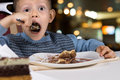 Hungry little boy gobbling down a slice of cake