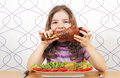 Hungry little girl eating turkey drumstick big Stock Photography