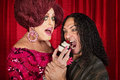 Hungry man and drag queen tall men eating cupcakes Stock Photos