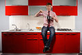 Hungry man portrait of young filching pan with soup on red kitchen Royalty Free Stock Image