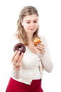 Hungry woman holding sweet muffin and donut Stock Photography