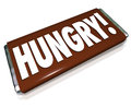 Hungry word chocolate candy bar wrapper hunger on a brown to illustrate a or craving for junk food and sugar snacks Royalty Free Stock Photography