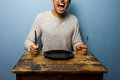Hungry young man is screaming for his dinner at old table Royalty Free Stock Photos