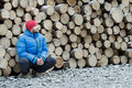Hunkering worker having a rest at pile of logged is firewood background outdoors in winter mountain forest Stock Images