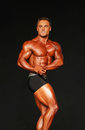 Hunky bodybuilder hits side chest pose handsome anthony catapano strikes a in the classic physique finals of the npc universe in Royalty Free Stock Images
