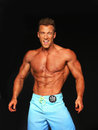 Hunky male bodybuilder strikes a pose handsome nicholas williamson poses in the men s physique finals of the npc universe held in Royalty Free Stock Image