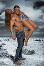 Hunky male carrying female model with no shirt sexy with nice legs Royalty Free Stock Image