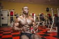 Hunky muscular black bodybuilder working out in gym exercising back on machine Royalty Free Stock Image