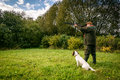 Hunter aiming with dog with his rifle Stock Image