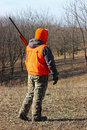 Hunter in blaze orange a field wearing camouflage and Royalty Free Stock Photos