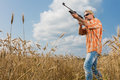 Hunter in cap and sunglasses aiming a gun at field Royalty Free Stock Photo