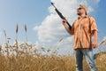 Hunter on cap and sunglasses aiming a gun at field Royalty Free Stock Photo