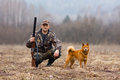 Hunter with a dog on the field sits Stock Images