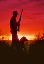 Hunter and dog silhouette a bird stands with gun at sunrise with his silhouetted Royalty Free Stock Photography
