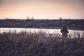 Hunter man in rural field in expectation of hunting during sunrise with copy space camouflage shotgun standing at river bank Stock Images