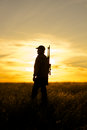 A hunter with rifle silhouetted against a sunset Royalty Free Stock Images